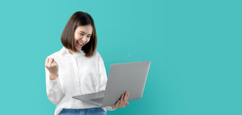 Mujer asiática joven que sonríe sosteniendo el ordenador portátil con la mano del puño y emocionado para el éxito en fondo azul c fotografía de archivo libre de regalías