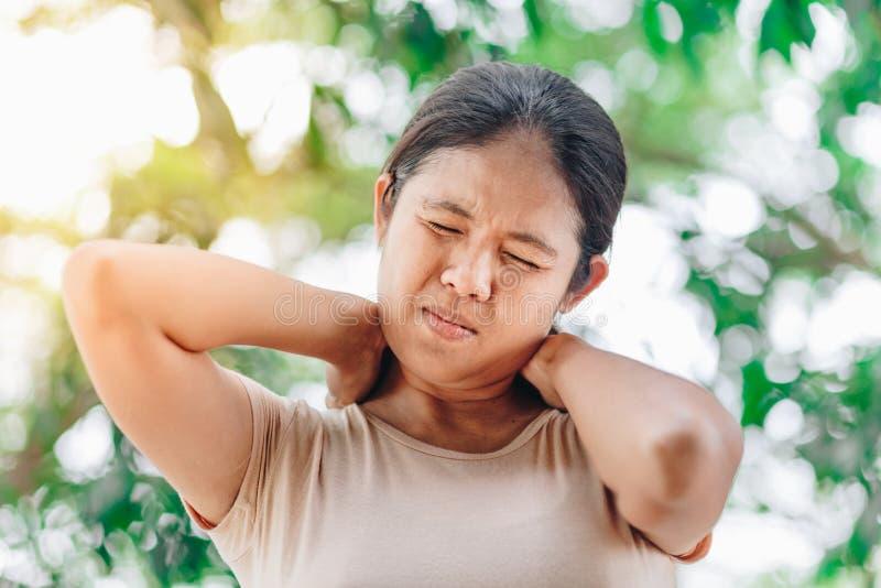 Mujer asiática joven que sufre de dolor de cuello imagen de archivo