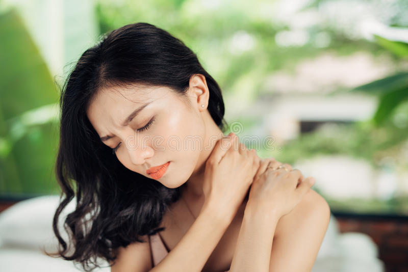 Mujer asiática joven que sufre de dolor de cuello mientras que se sienta en cama foto de archivo libre de regalías