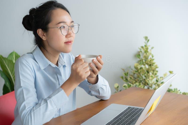 Mujer asiática joven que trabaja en el ordenador portátil en el escritorio de Ministerio del Interior y gozando de la taza de caf imagen de archivo libre de regalías