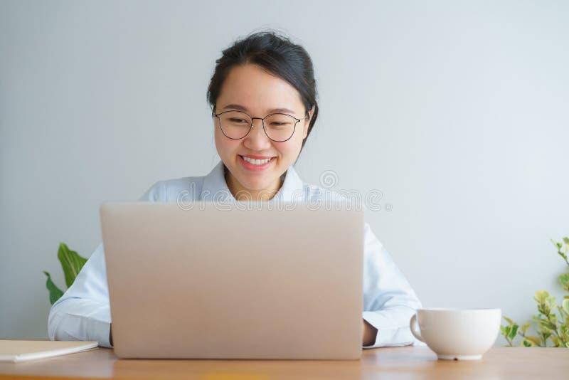 Mujer asiática joven que trabaja en el ordenador portátil en el escritorio de Ministerio del Interior fotografía de archivo