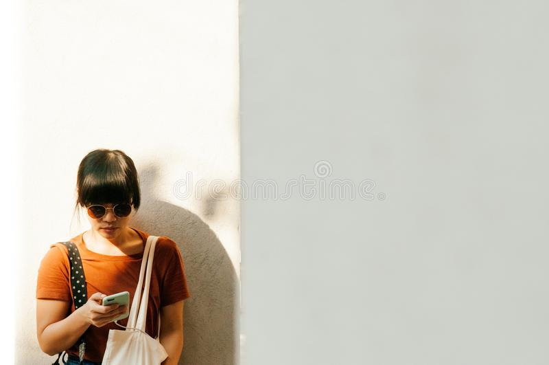 Mujer asiática joven que usa el teléfono móvil bajo luz del sol con c blanca imagen de archivo