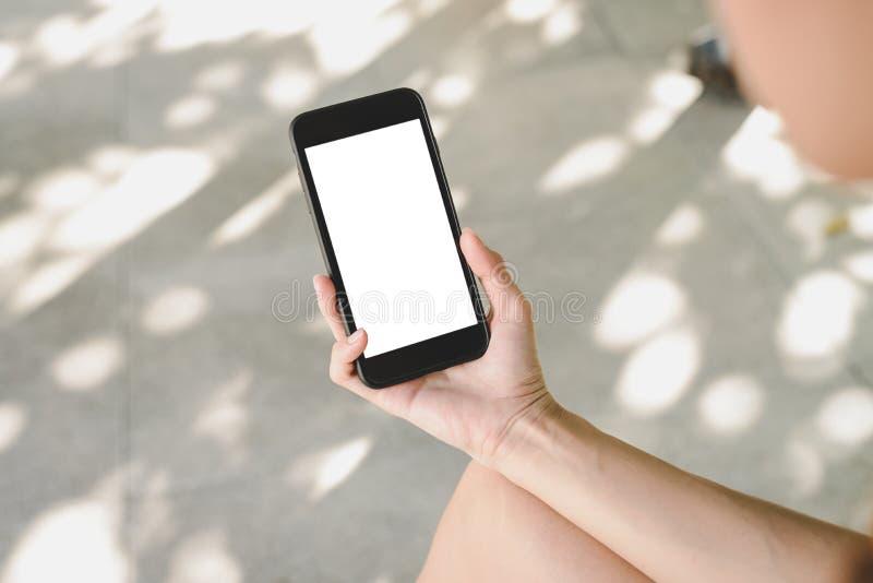Mujer asiática joven que usa mofa del smartphone encima de la pantalla blanca en blanco en café fotografía de archivo libre de regalías