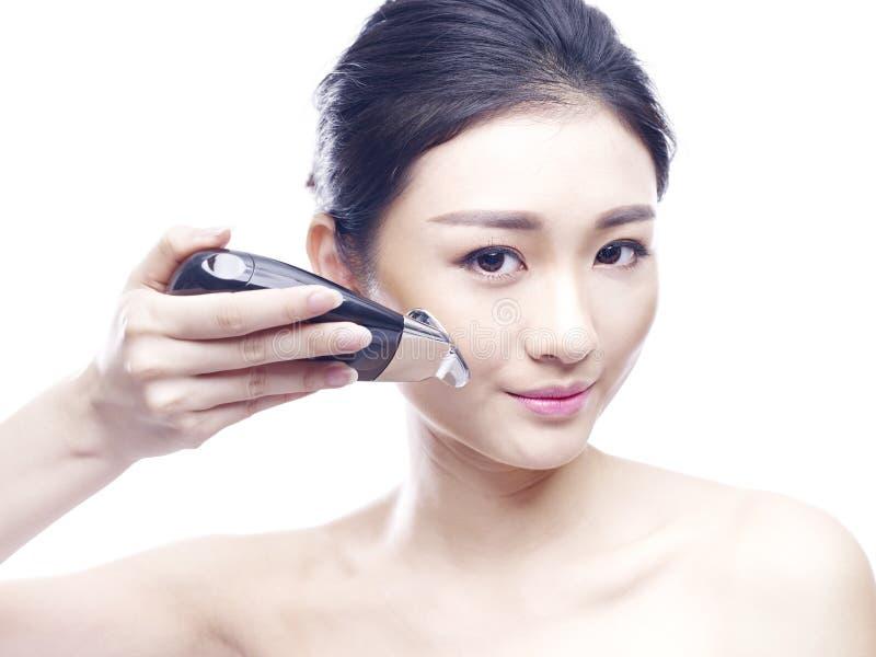 Mujer asiática joven que usa un dispositivo del balneario de la cara imagen de archivo