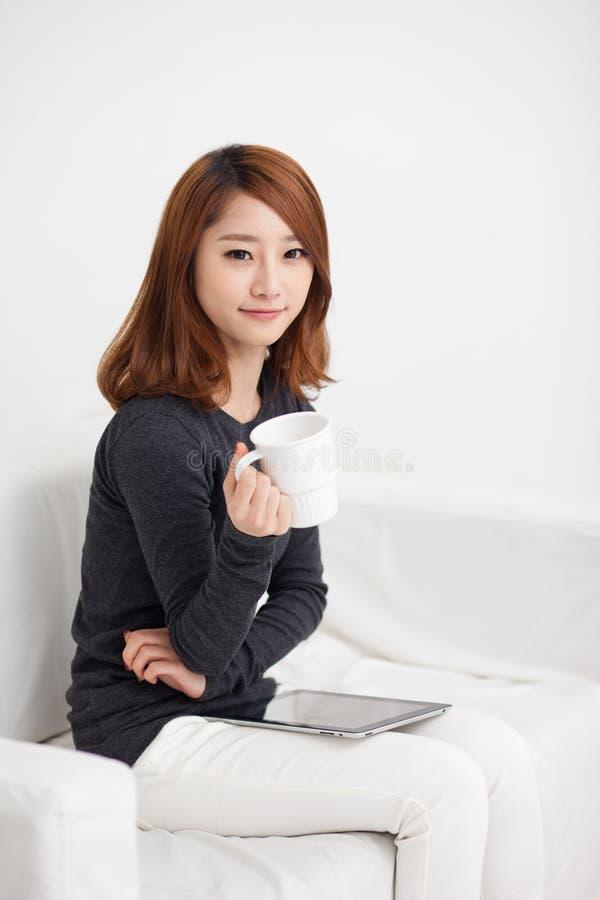 Mujer asiática joven que usa una PC de la pista foto de archivo