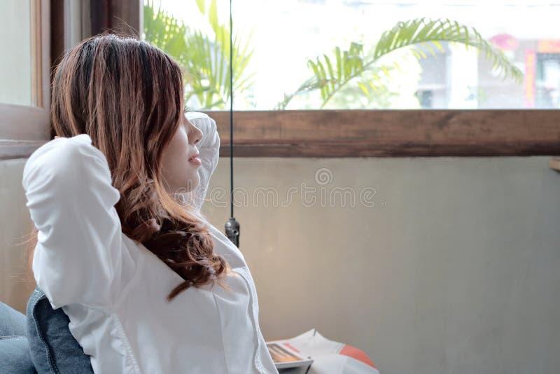Mujer asiática joven relajada que asiste y que mira a través de ventanas lejos la cafetería contra fondo del espacio de la copia imagenes de archivo