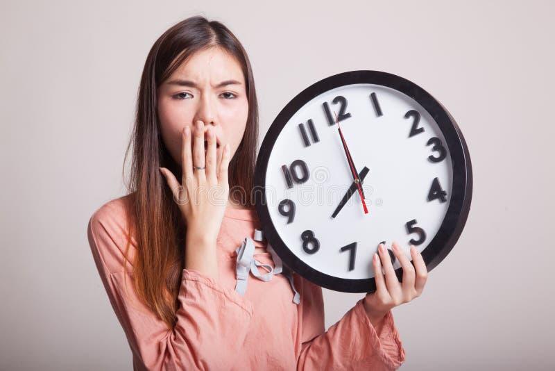 Mujer asiática joven soñolienta con un reloj por la mañana foto de archivo