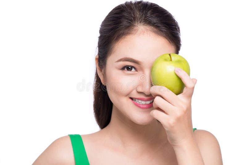 Mujer asiática joven sonriente atractiva que come la manzana verde aislada foto de archivo libre de regalías