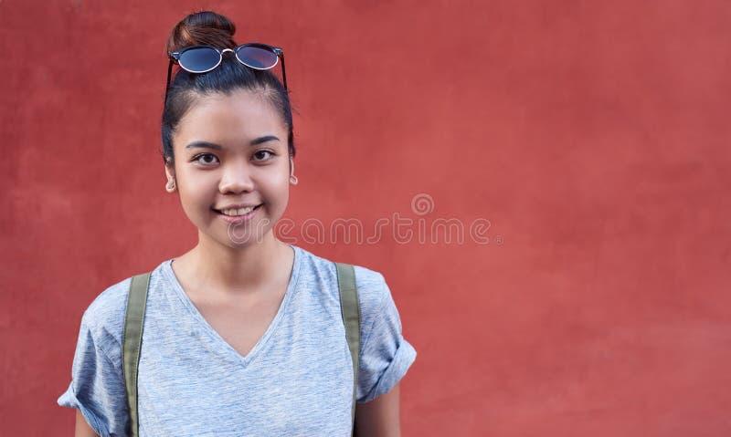 Mujer asiática joven sonriente que hace una pausa una pared afuera imágenes de archivo libres de regalías