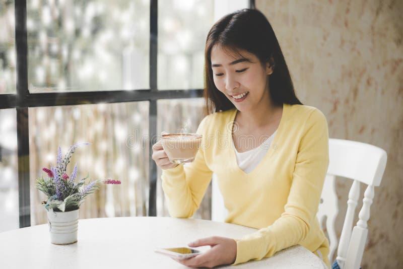 Mujer asiática joven sonriente que se sienta en alféizar y té de consumición en la ventana en sitio Buena mañana el día de invier fotografía de archivo