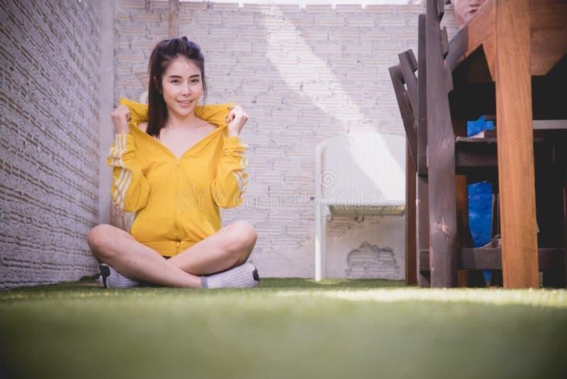 Mujer asiática joven sonriente que se sienta en hierba verde imagen de archivo
