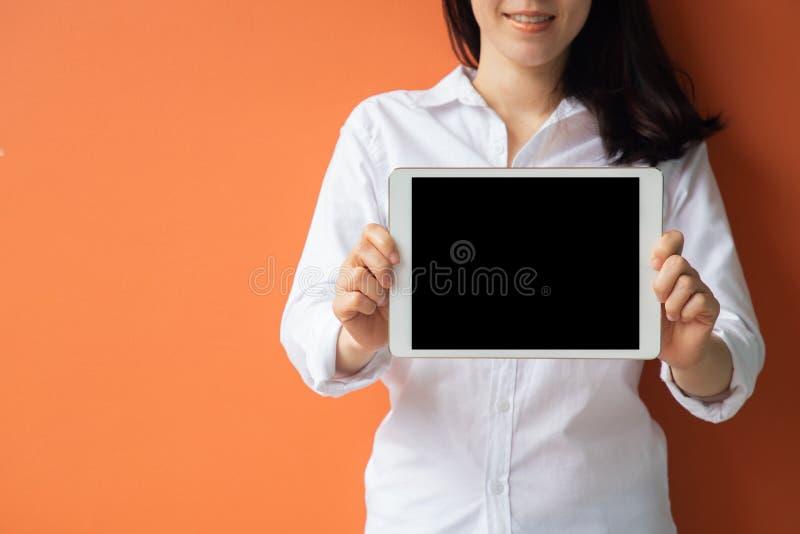Mujer asiática joven sonriente que sostiene la tableta de la pantalla en blanco, móvil, teléfono celular imágenes de archivo libres de regalías