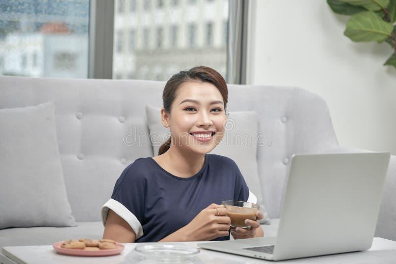 Mujer asiática joven sonriente que sostiene la taza de café mientras que se sienta en el piso con el ordenador portátil y la tarj imagen de archivo