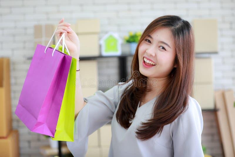 Mujer asiática joven y hermosa celebrando varia compras coloridas imagen de archivo