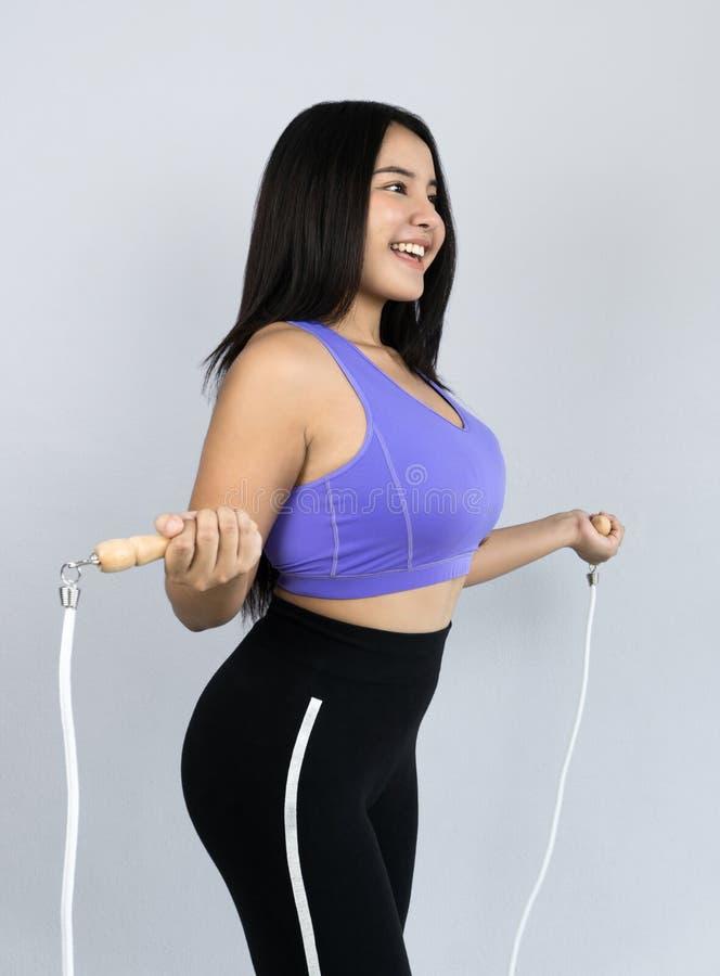Mujer asiática joven y hermosa en saltar de la ropa de deportes imagen de archivo libre de regalías