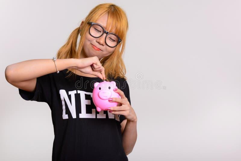 Mujer asiática linda joven del empollón que pone la moneda en la hucha fotos de archivo libres de regalías