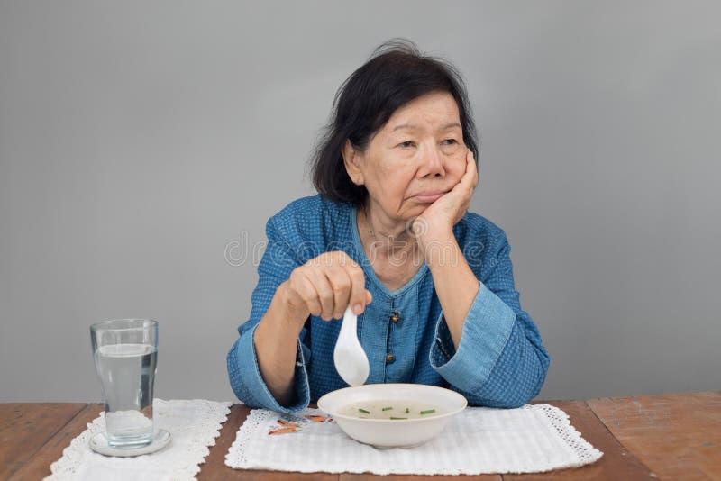 Mujer asiática mayor aburrida con la comida foto de archivo libre de regalías