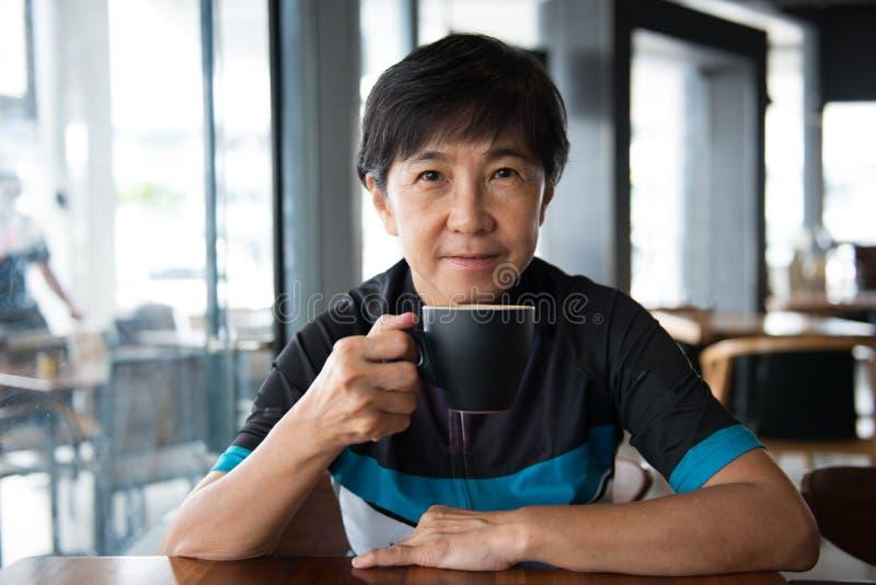 Mujer asiática mayor con café en jersey de ciclo fotografía de archivo libre de regalías