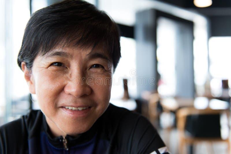 Mujer asiática mayor con café en jersey de ciclo fotografía de archivo