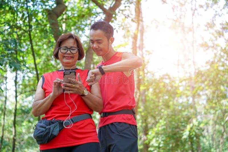 Mujer asiática mayor con el hombre o el instructor personal que comprueba tiempo fotografía de archivo libre de regalías