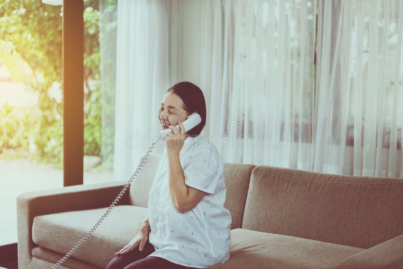 Mujer asiática mayor feliz que habla en el teléfono en la sala de estar fotos de archivo