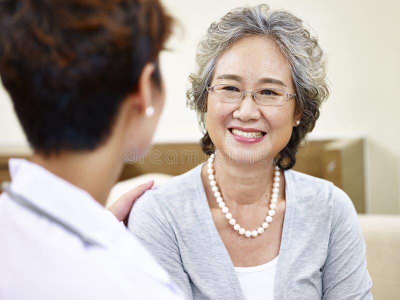 Mujer asiática mayor que habla con el médico de cabecera foto de archivo
