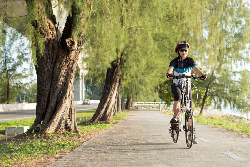 Mujer asiática mayor que monta una bicicleta imagen de archivo