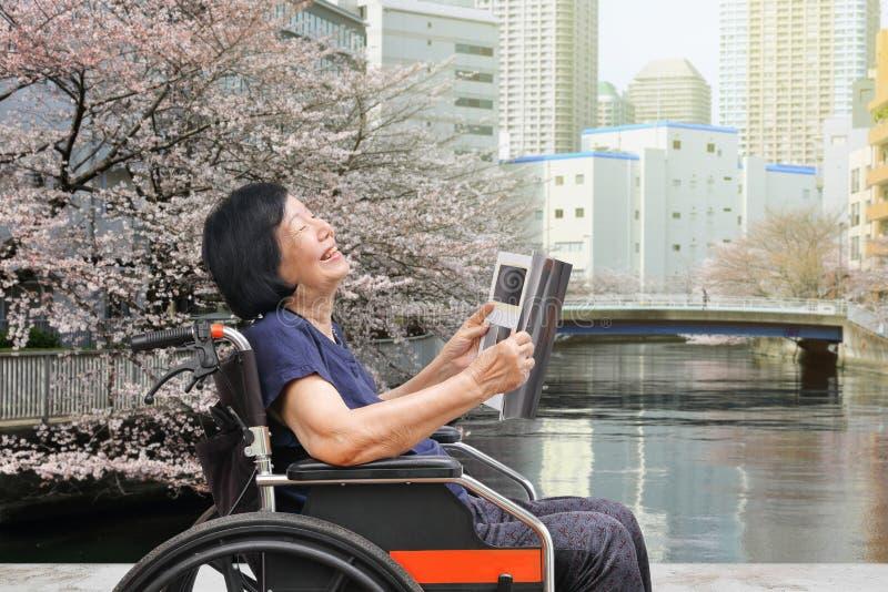 Mujer asiática mayor que ríe mientras que lee la revista en parque fotos de archivo libres de regalías