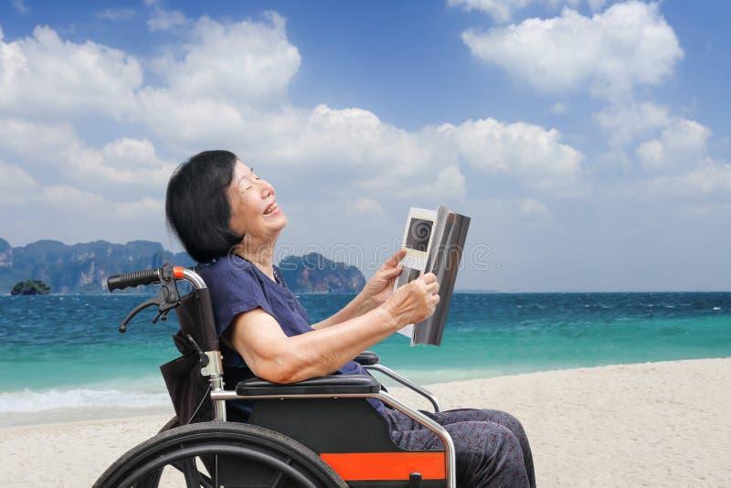 Mujer asiática mayor que ríe mientras que lee la revista en la playa fotografía de archivo libre de regalías