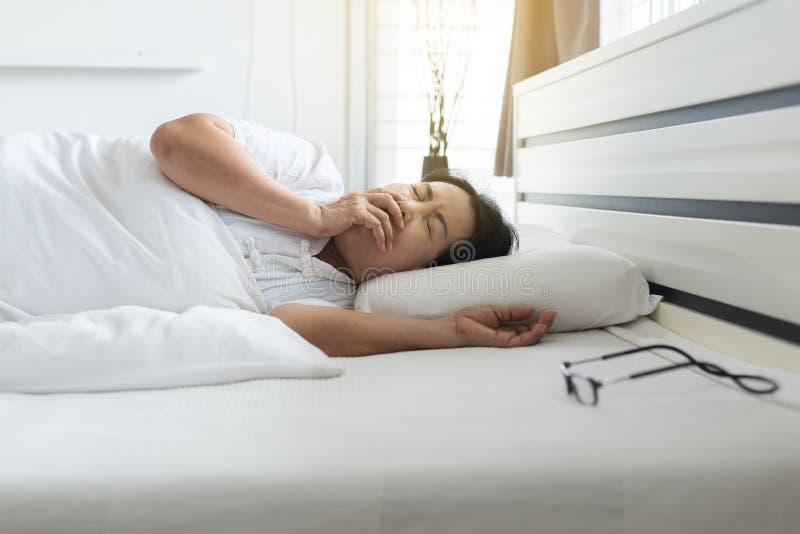 Mujer asiática mayor que tose y que coloca en su cama, concepto de salud imágenes de archivo libres de regalías