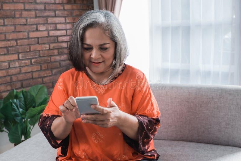 Mujer asiática mayor que usa su teléfono elegante fotografía de archivo