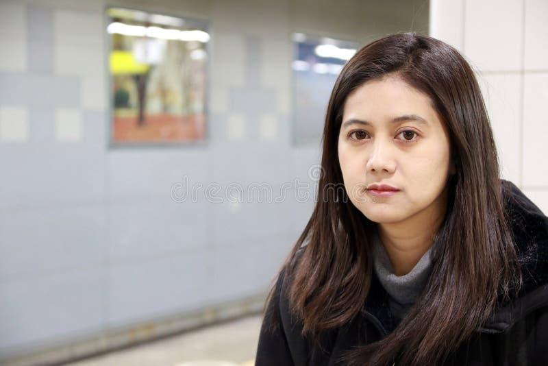 Mujer asiática, pelo largo, en ropa negra, retrato que se sienta interior imagen de archivo