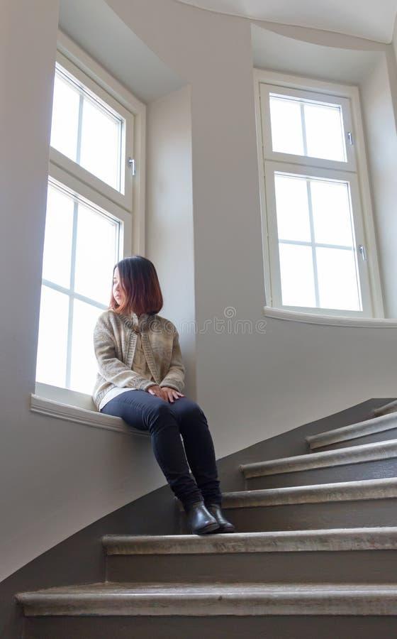 Mujer asiática por la ventana foto de archivo libre de regalías