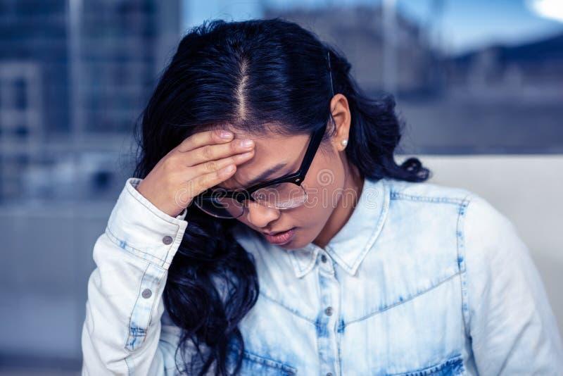 Mujer asiática preocupada con la mano en cara imagenes de archivo