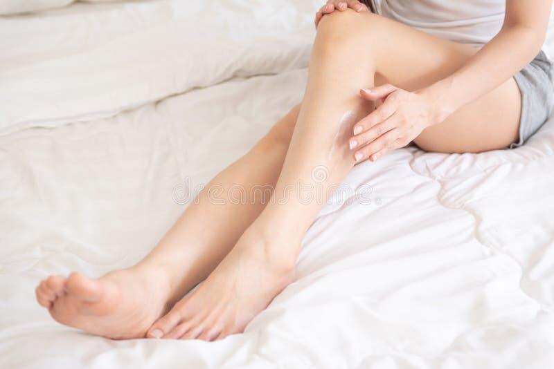 Mujer asiática que aplica la loción del cuerpo en sus piernas fotografía de archivo libre de regalías