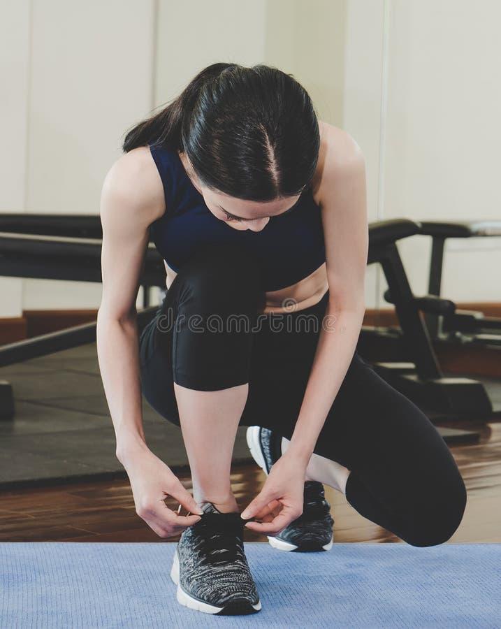 Mujer asiática que ata el cordón en gimnasio de la aptitud foto de archivo