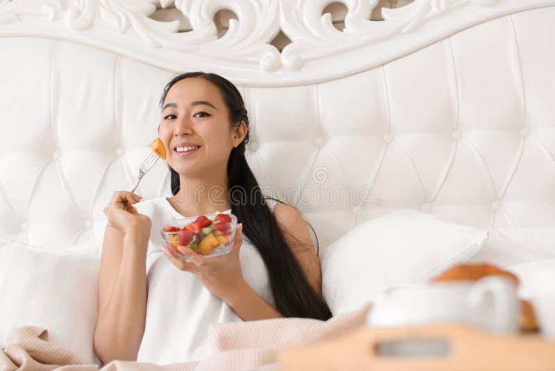 Mujer asiática que come la ensalada de fruta sana para el desayuno en casa fotografía de archivo