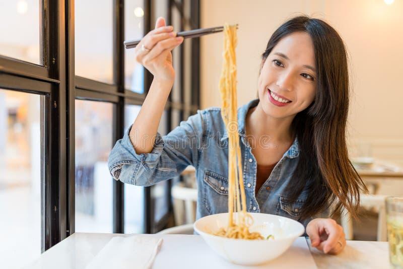 Mujer asiática que come los tallarines en restaurante chino fotografía de archivo