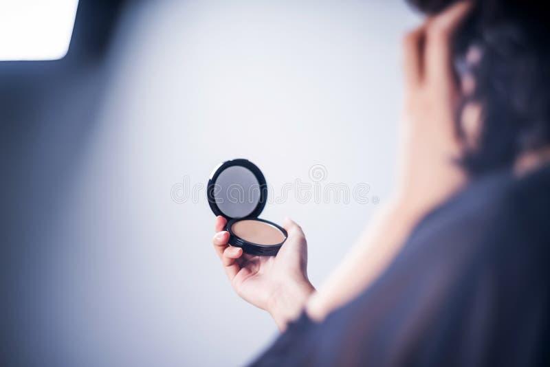 Mujer asiática que compone mirando el tiro del estudio del espejo fotos de archivo libres de regalías