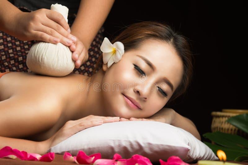 Mujer asiática que consigue masaje herbario tailandés de la compresa imagenes de archivo