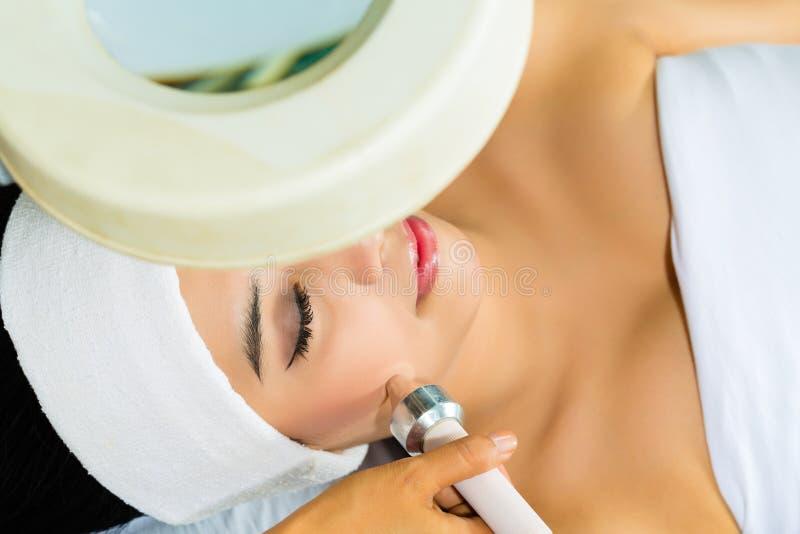 Mujer asiática que consigue un tratamiento facial en balneario imagenes de archivo
