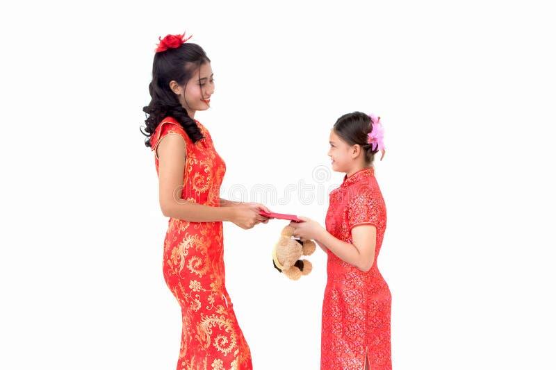 Mujer asiática que da sobres rojos a los niños, celebrando chino fotos de archivo libres de regalías