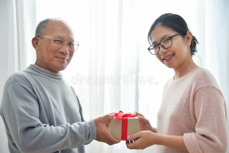 Mujer asiática que da una caja de regalo marrón al hombre mayor imagen de archivo libre de regalías