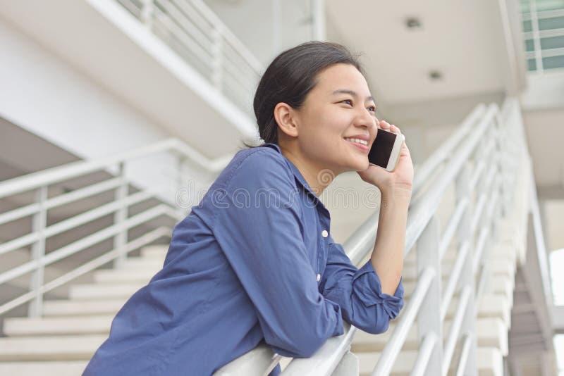 Mujer asiática que disfruta de la conversación telefónica con el amigo imagenes de archivo