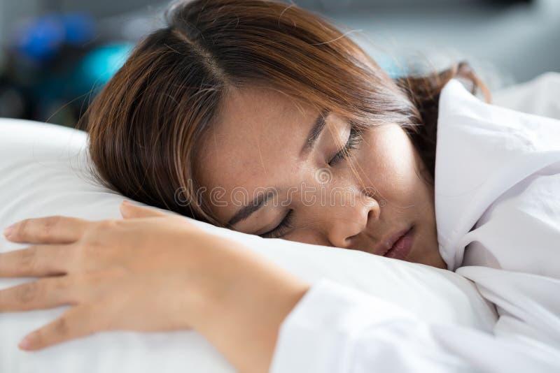 Mujer asiática que duerme en cama imagenes de archivo