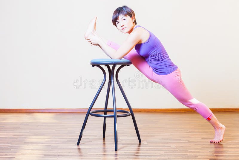 Mujer asiática que estira para el ejercicio de la yoga en casa por las sillas fotografía de archivo libre de regalías