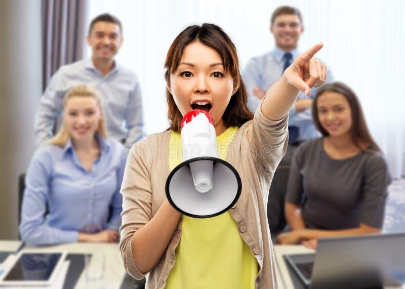 Mujer asiática que habla al megáfono sobre el equipo de la oficina imagenes de archivo
