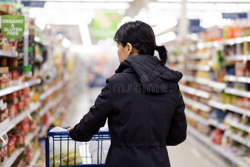Mujer asiática que hace compras de ultramarinos en supermercado imágenes de archivo libres de regalías