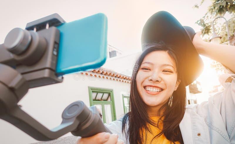 Mujer asiática que hace el vídeo con el cardán del smartphone al aire libre - muchacha asiática feliz que se divierte con tendenc foto de archivo libre de regalías