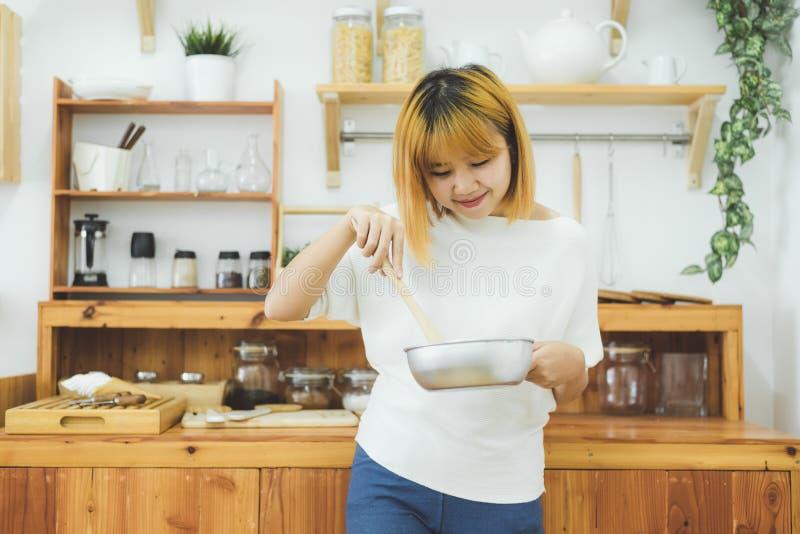 Mujer asiática que hace la comida sana que coloca la sonrisa feliz en la cocina que prepara la ensalada fotografía de archivo libre de regalías